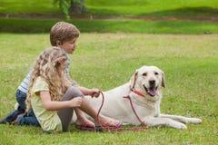 Twee jonge geitjes met huisdierenhond bij park Royalty-vrije Stock Foto's