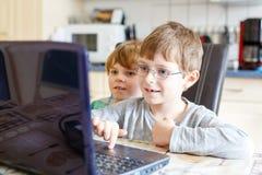 Twee jonge geitjesjongens die het online spel van de schaakraad op computer spelen stock afbeelding