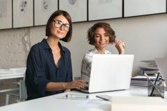Twee jonge gelukkige vrouwen die door de lijst werken stock afbeeldingen