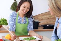 Twee jonge gelukkige vrouwen koken in de keuken De vrienden hebben pret terwijl het preapering van gezonde en smakelijke maaltijd Royalty-vrije Stock Foto's