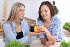 Twee jonge gelukkige vrouwen maken online het winkelen door tabletcomputer en creditcard De vrienden gaan in Th koken Royalty-vrije Stock Foto's