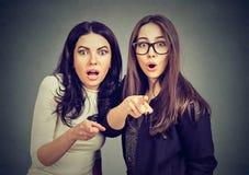 Twee jonge geschokte vrouwen zijn doen schrikken over iets die vingers richten op camera royalty-vrije stock afbeeldingen