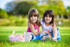 Twee jonge glimlachende meisjes die in het gras koesteren