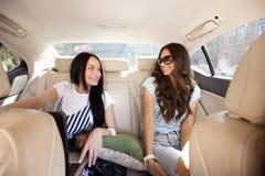 Twee jonge glimlachende mooie meisjes met lang haar, gekleed in toevallige stijl, zitten in de achterbank van een auto met a stock afbeeldingen