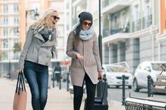 Twee jonge glimlachende mooie vrouwen die in warme kleren onderaan de stadsstraat lopen met een en reiskoffer, vrouwen die lachen royalty-vrije stock foto's