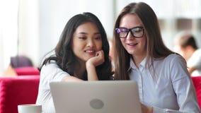 Twee jonge glimlachende onderneemstervrienden die informele teamvergadering hebben die laptop met behulp van stock videobeelden