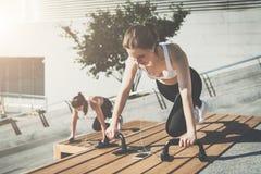 Twee jonge glimlachende vrouwen, meisjes in sportkleding het doen oefent terwijl het luisteren aan muziek uit Training, die op st stock afbeelding