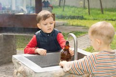 Twee jonge jongens die een fles water vullen Stock Foto