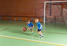 Twee jonge jongens die een spel van basketbal spelen Royalty-vrije Stock Foto's