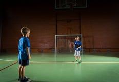Twee jonge jongens die met een basketbal spelen stock foto's