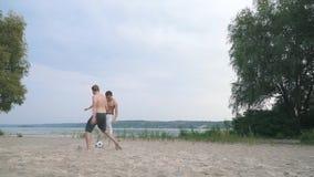 Twee jonge jongens die voetbal spelen bij de rivierconcurrentie tussen mensen de Jonge mens scoresvrienden is hebben samen een pr stock footage