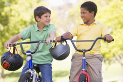 Twee jonge jongens op fietsen die in openlucht glimlachen Royalty-vrije Stock Foto's