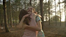 Twee jonge Kaukasische meisjes die in kleding in het hout, het lachen koesteren, die aard op de achtergrond rond voor de gek houd stock video