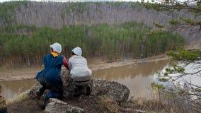 Twee jonge Kaukasische wijfjes op een klippengevaar die neer aan rivier kijken royalty-vrije stock foto's