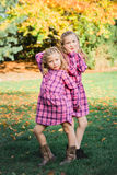 Twee Jonge Kaukasische Zusters slaan stellen in de Aanpassing van Roze Flanelkleding Royalty-vrije Stock Foto