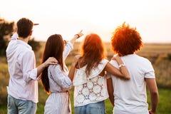 Twee jonge kerels en twee meisjes gekleed in modieuze kleren bevinden zich op het gebied en kijken voor hen op a stock afbeelding