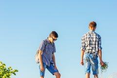 Twee jonge kerels tegen de hemel, een verhouding met elkaar stock afbeeldingen
