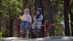 Twee jonge kinderen die bananen eten die op de bank zitten stock video