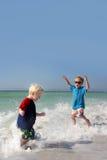 Twee Jonge Kinderen die en in Oceaanwater spelen bespatten Stock Foto