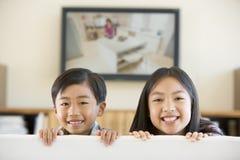 Twee jonge kinderen in ruimte met het vlakke scherm Stock Foto's
