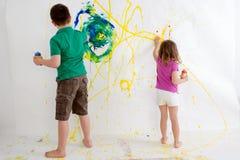 Twee jonge kinderen schilderen het uit de vrije hand op een muur Stock Afbeeldingen