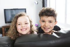 Twee jonge kinderen in woonkamer met het vlakke scherm stock afbeelding