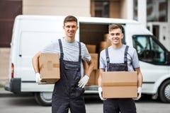 Twee jonge knappe glimlachende arbeiders die uniformen dragen bevinden zich naast het bestelwagenhoogtepunt die van dozen dozen i royalty-vrije stock fotografie