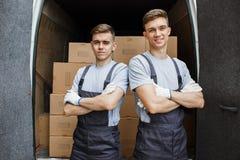 Twee jonge knappe glimlachende arbeiders die uniformen dragen bevinden zich voor het bestelwagenhoogtepunt van dozen Huisbeweging stock afbeelding