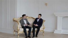 Twee jonge knappe mensenzitting op een uitstekende bank stock videobeelden