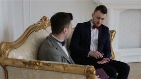 Twee jonge knappe zakenlieden die zaken bespreken, die op een uitstekende bank zitten stock footage