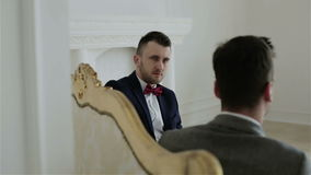 Twee jonge knappe zakenlieden die zaken bespreken, die op een uitstekende bank zitten stock video