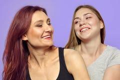 Twee jonge lachende vrouwen, één Kaukasisch blonde, een andere één Latijn Mooie diversiteit, pret en strakke verhouding, sterke e royalty-vrije stock foto's