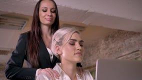 Twee jonge lesbiennes in bureau, mooie bedrijfsvrouw die andere vrouw masseren, prettig en gelukkig stock videobeelden