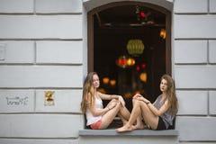 Twee jonge leuke meisjes die bij het venster van een nachtclub zitten Pret Stock Fotografie