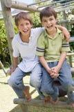 Twee jonge mannelijke vrienden bij speelplaats het glimlachen Stock Afbeelding