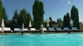 Twee jonge mannen storen jonge mooie vrouwenzitting op de rand van de pool wanneer zij springen stock videobeelden