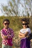 Twee jonge Marokkaanse zusters die met zonnebril en aardbac stellen Stock Fotografie