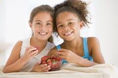 Twee jonge meisjes die aardbeien eten Royalty-vrije Stock Foto