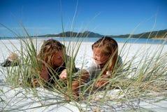 Twee jonge meisjes die achter gras op strand verbergen Stock Afbeelding