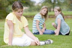 Twee jonge meisjes die ander jong meisje in openlucht intimideren stock foto