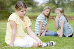 Twee jonge meisjes die ander jong meisje in openlucht intimideren Stock Foto's