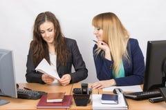 Twee jonge meisjes die in een bureau werken, makend een document vliegtuig, en de tweede bekijkt haar in verrassing Royalty-vrije Stock Afbeeldingen