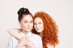 Twee jonge meisjes die elkaar koesteren Stock Afbeeldingen