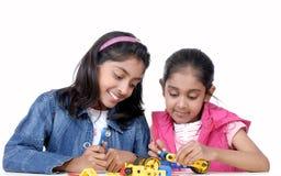 Twee jonge meisjes die met mechanische blokken spelen Stock Fotografie