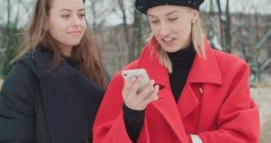 Twee jonge meisjes die mobiele telefoon in een stad met behulp van stock videobeelden