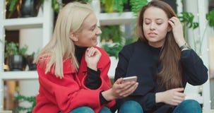 Twee jonge meisjes die mobiele telefoon in een stad met behulp van stock footage