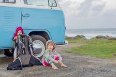 Twee jonge meisjes die naast oude stijl minivan kampeerauto zitten royalty-vrije stock fotografie