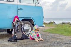 Twee jonge meisjes die naast oude stijl minivan kampeerauto zitten royalty-vrije stock foto