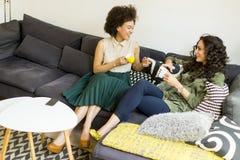 Twee jonge meisjes die op de bank in de ruimte, het drinken koffie zitten Royalty-vrije Stock Foto