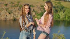 Twee jonge meisjes die op de camera op riverbank stellen stock video